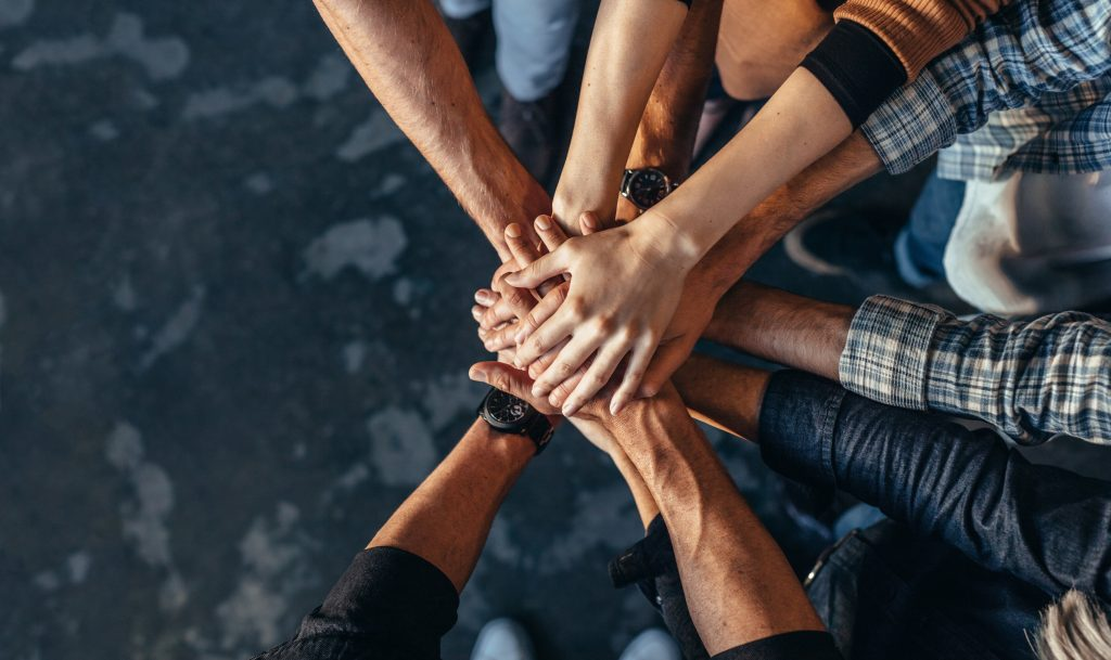 Top view of creative professionals putting their hands together as a symbol of teamwork, cooperation and unity. Stack of hands of men and woman.